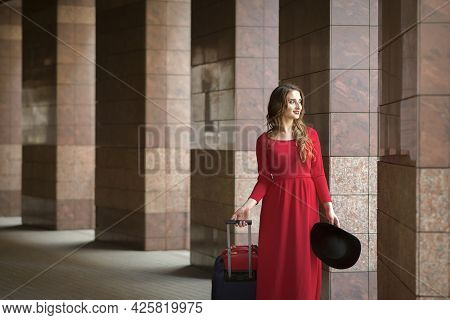 Beautiful Young Caucasian Woman Wearing Red Long Dress With A Suitcase Standing In Columns