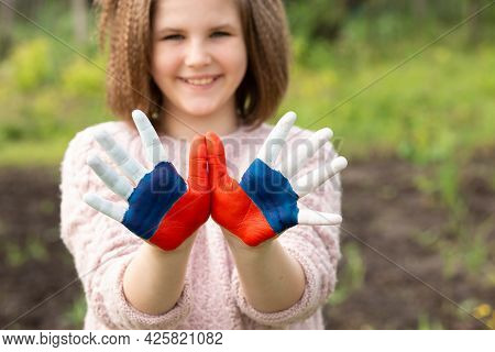Child Girl Show Hands Painted In Russia Flag Colors Walking Outdoor, Focus On Hands. Day Of Russian