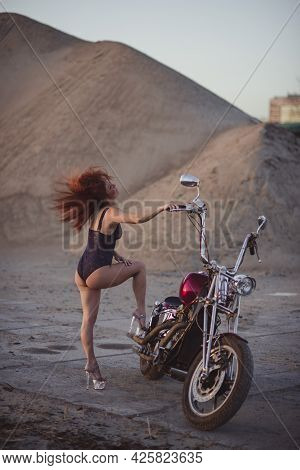 Red-haired Woman In Sexy Lingerie In High Heels Sits On A Motorcycle. Attractive Red-haired Girl Sit