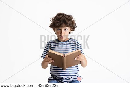 One Caucasian Preschool Boy Sitting And Reading Book Isolated On White Studio Background. Copyspace.