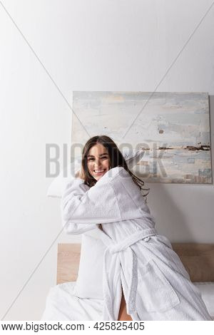 Playful Young Woman In Bathrobe Holding Pillow While Looking At Camera