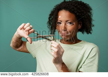 Young woman with vitiligo cutting her hair and looking at camera isolated over blue wall