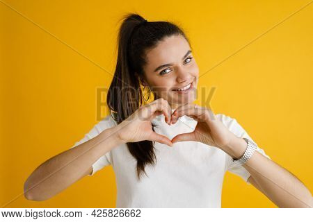Young brunette woman smiling and showing heart sign isolated over yellow background