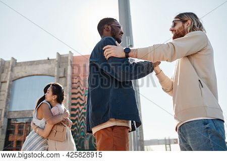 Low Angle View At Friends Meeting Outdoors In Urban City Setting Lit By Sunlight, Focus On Two Men S