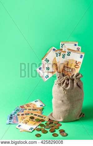 Money Bag On A Green Background. Euro Bills Sticking Out Of The Bag. Wealth Concept.