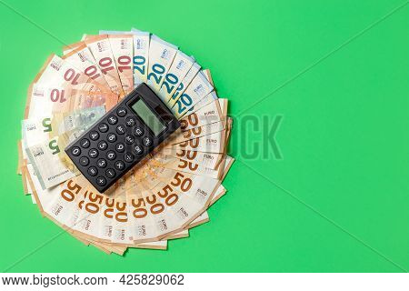 Money. Cash. Euro Bills And Calculator On The Green Background. The Salary. Poverty And Wealth Conce