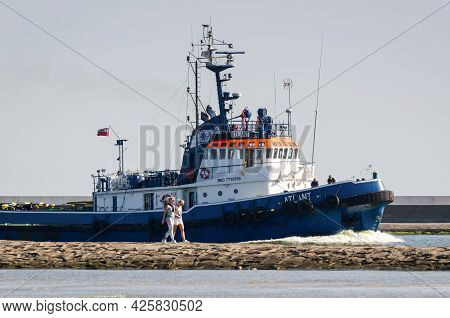 Swinoujscie, West Pomeranian - Poland - 2020: Holidaymakers Walk On The Breakwater And Tugboat Goes