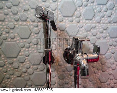 Stock Photo Of Hand Using Silver Bidet Shower Or Bum Gun With Tap On Wall At Kolhapur, Maharashtra ,