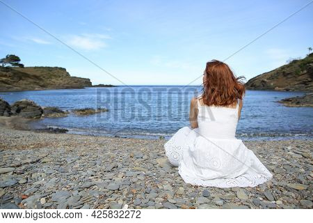 Back View Of A Woman In White Dress Sitting On The Beach Contemplating Views