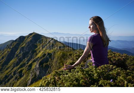 Beautiful Young Woman Sitting On Grassy Hill In Lotus Position And Doing Gyan Mudra Hand Gesture Whi