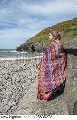 Vertical Image Of Mature Woman In Fifties Wrapped In A Red Blanket At Beach