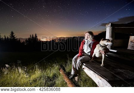 Young Woman In The Mountains Watching Beautiful Starry Night From A Wooden Hut Porch Together With H