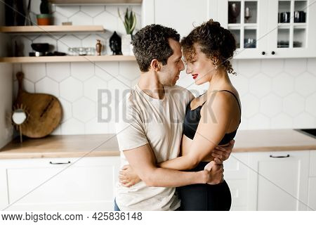 Happy Millennial Husband And Wife Hug Cuddle And Enjoy Romantic Moment In Modern Kitchen, Loving You