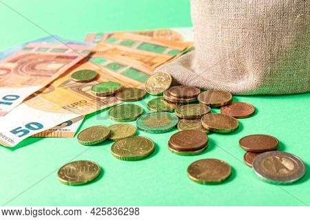 Euro Bills And Small Change Cents On A Green Background. Concept.