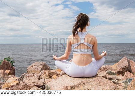 Back View Of Brunette Woman In Headphones And Sportswear Sitting In Lotus Pose While Meditating Near