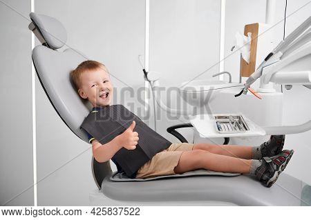 Horizontal Side View Snapshot Of A Little Smiling Boy Wearing Black Bib, Sitting In Dentist Chair, T