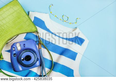 Summer Fashion Flatlay With Striped Top, Green Baguette Bag, Beaded Necklace And Blue Instant Camera