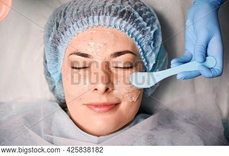 Close Up Of Beautician Hand Applying Cosmetic Mask On Young Woman Face. Female Client In Disposable