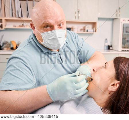 Close Up Of Male Dentist In Medical Face Mask And Sterile Gloves Performing Dental Procedure In Mode