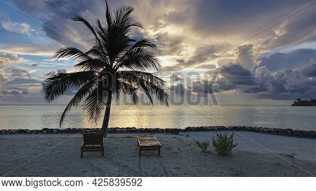 Sunset In The Maldives. There Are Two Sun Loungers On The Sandy Beach. Palm Tree Against The Backgro