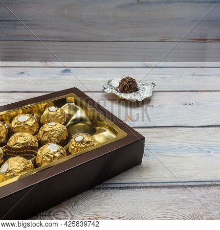A Brown Cardboard Box Is Open And Filled With Chocolates Wrapped In Gold Foil. One Candy Is Unfolded