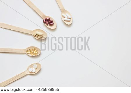 Dietary Supplements And Vitamins On Wooden Spoons On A White Background. Copy Space. The Concept Of