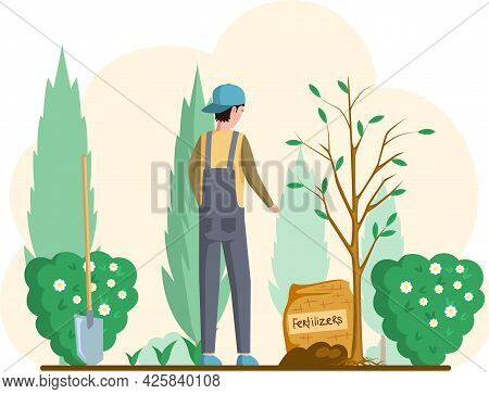 Man With Shovel Standing Near Tree In Garden. Guy Buries Seedling In Ground For Planting Trees. Prof