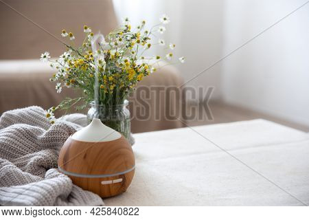 Modern Oil Aroma Diffuser In The Living Room On The Table With Knitted Element And Flowers Copy Spac