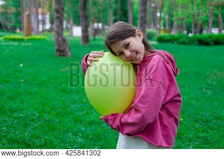 Sweet Tween Brunette Girl In Pink Holding Yellow Balloon Outdoors.
