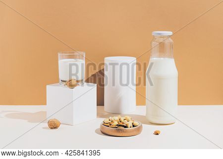 Glass And A Bottle With Vegan Milk From Various Nuts With White Geometric Figures On Sunlit Backgrou