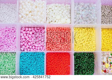Creative Flatlay Of Different Seed And Pearl Beads In The Box On Pink Background.