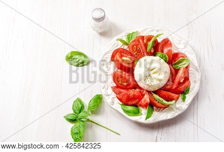 Burrata Salad On White Plate. Top View Of Salad With Burrata Cheese And Basil Leaves On White Table.