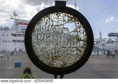 A Vintage Rusty Metal Dark Porthole With Broken Glass. A Broken Window.