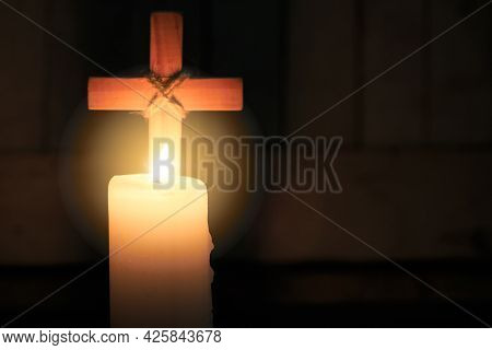 The Candle Glows In Front Of The Cross. Christmas, Easter And Religious Background With Copy Space.