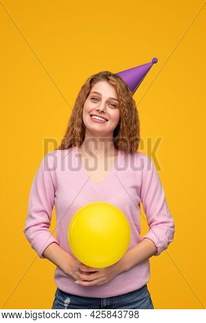 Optimistic Young Blond Female With Party Hat And Balloon Smiling And Looking At Camera While Celebra