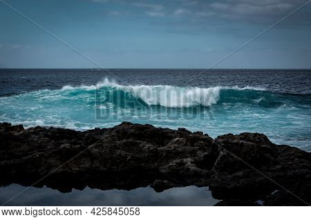 An Azzure Wave Crushing On Black Vulcanic Rocks Of Playa De La Arena, Tenerife, Canary Islands, Spai