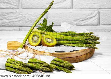 Fresh Green Fruit And Vegetable: Kiwi, Mint And Asparagus On Wooden Board On White Background. Healt