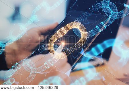 Close Up Of Hands Using Digital Pad With Creative Glowing Blockchain Hologram On Blurry Desktop Back