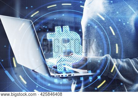 Hacker In Hoodie Using Laptop Computer With Glowing Bitcoin Interface In Blurry Office Interior. Hac