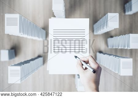 Top View Of Hand With Paperwork Stack On Wooden Background. Workload And Bureaucracy Concept