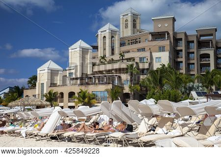 Grand Cayman, Cayman Islands - March 8, 2013:  Guests Of Luxury Hotel Relax On Loung Chairs On The B
