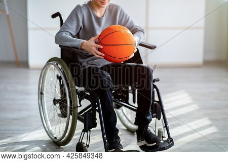 Cropped View Of Disabled Teenager In Wheelchair Holding Basketball At Home. Impairment And Sports Co
