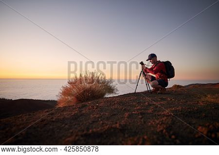 Young Man During Photographing Landscape On Top Of Hill Above Clouds. Hobby Photographer Waiting For