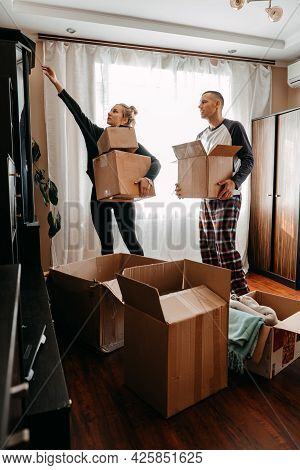 Moving Day, New Home, Unpacking Boxes. Happy Couple In Their New Apartment Is Having Fun With Cardbo