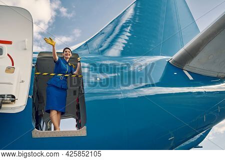 Happy Dark-haired Air Hostess Standing In The Open Aircraft Doorway