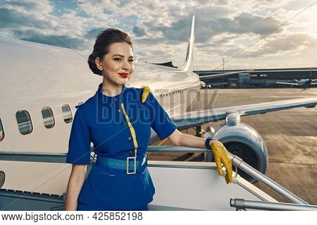 Dreamy Flight Attendant Standing On The Aircraft Steps