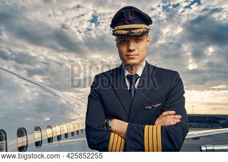 Serene Male Pilot With His Arms Crossed Looking Ahead