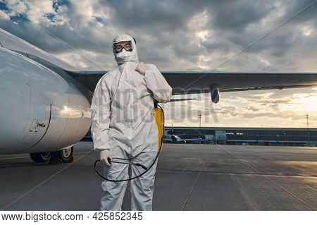 Man In A Hazmat Suit Standing At The Airdrome