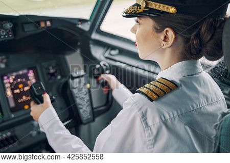 Serious Concentrated Female Aviator Piloting An Aircraft