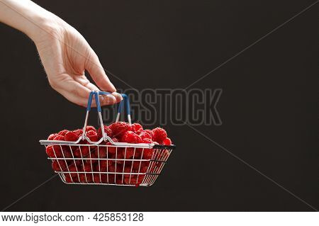 Girls Hand Holding A Mini Grocery Shopping Basket With Fresh Raspberries On A Dark Background